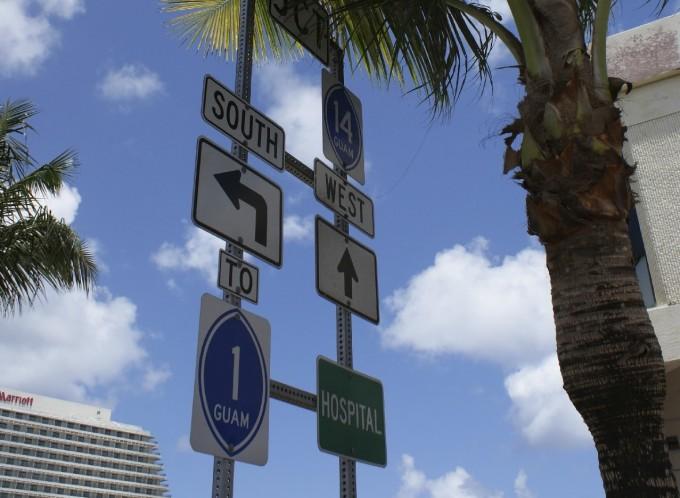 グアムの道路標識とヤシの木