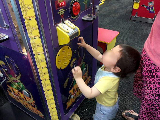 チャッキーチーズでチケットを挿入する1歳児