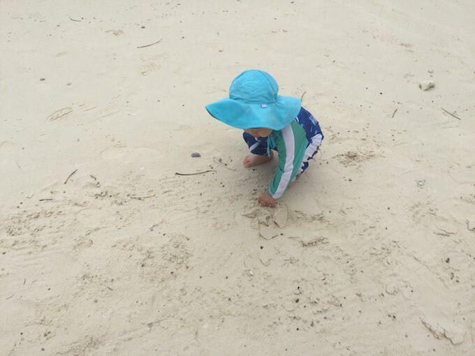 タモンビーチで砂遊びをする1歳児