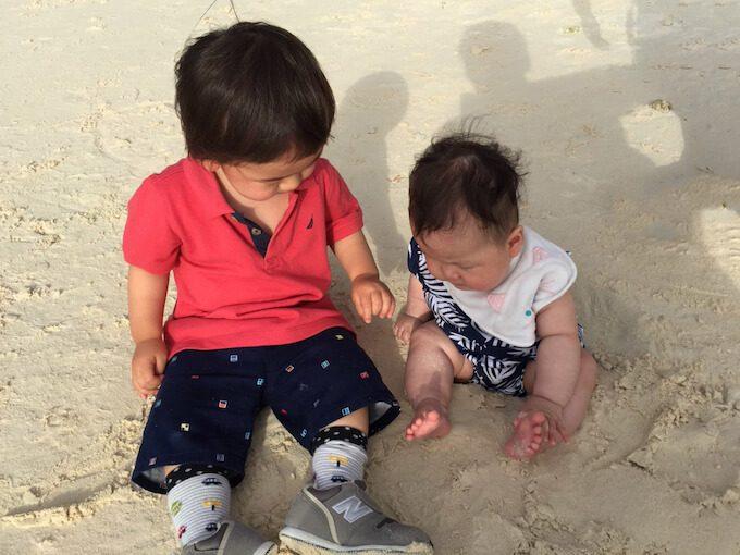 グアムのビーチの砂浜で遊ぶ1歳児と0歳児