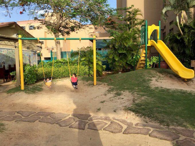 グアムでブランコに乗る1歳児と6ヶ月の子ども
