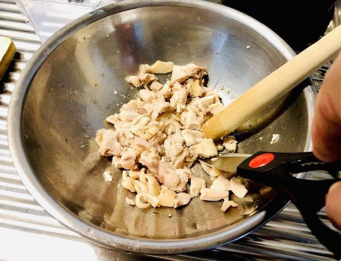 ハサミでカットしている焼いたチキン
